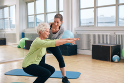 staff with old woman having hip exercise session