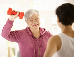 staff with old woman having shoulder exercise session