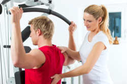 staff with man having back exercise session